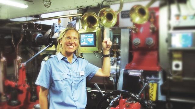 Eine Frau in blauem Hemd steht im Maschinenraum eines Schiffes.