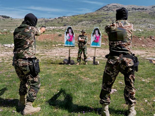 Zwei Soldaten schiessen auf zwei Plakate.