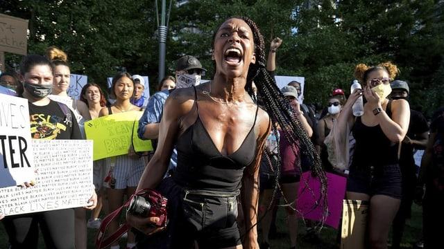 eine schwarze Frau schreit in eine Menschengruppe