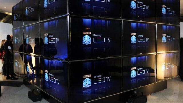 Ein grosser Würfel aus Fernseher mit einem Logo für die neueste Technologie