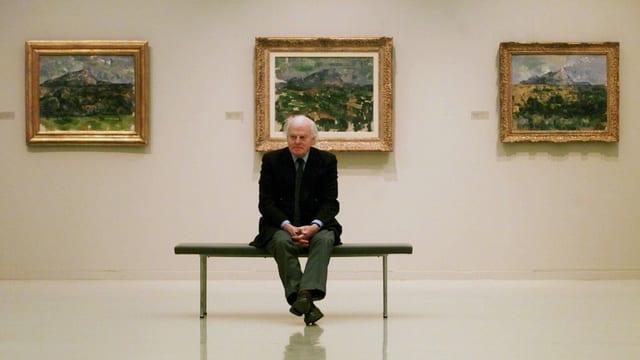 Eberhard Kornfeld sitzt in einem Museum vor drei Cezanne-Bildern.