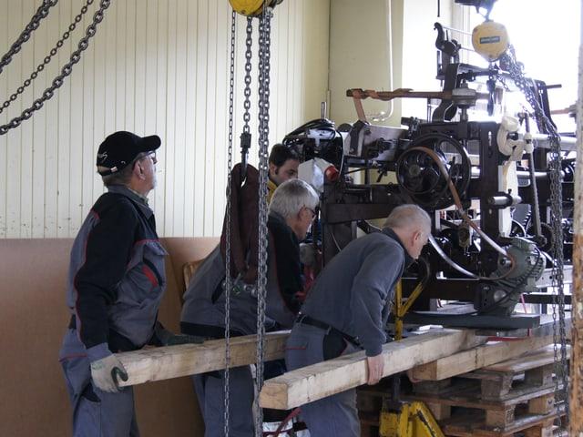 Der über 100-jährige Webstuhl wird im Inneren der Fabrik mit Hilfe von Kanthölzern auf ein Palett geschoben.
