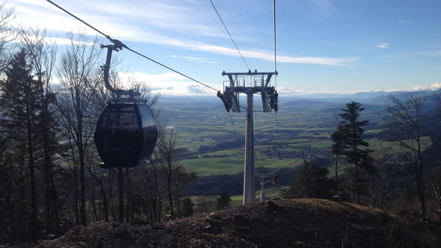 Gondeli an Seil, dahinter Sicht aufs Mittelland