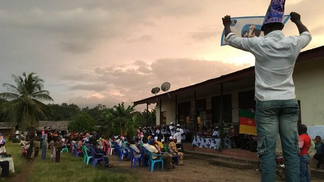 Einige Dutzend Dorfbewohner sitzen vor einem Haus, dort ist eine Art Bühne installiert.