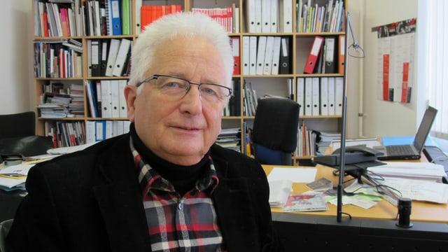 Beat Wyrsch in seinem Büro, hinter ihm ein Regal voller Bücher und Ordner.