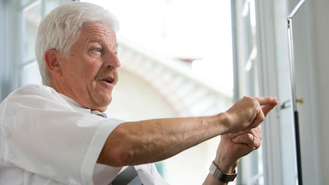 Ein älterer Herr gestikuliert mit seinen Händen vor einem offenen Fenster.