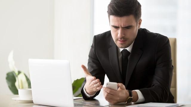 Ein Mann mit dem Handy vor dem Computer.