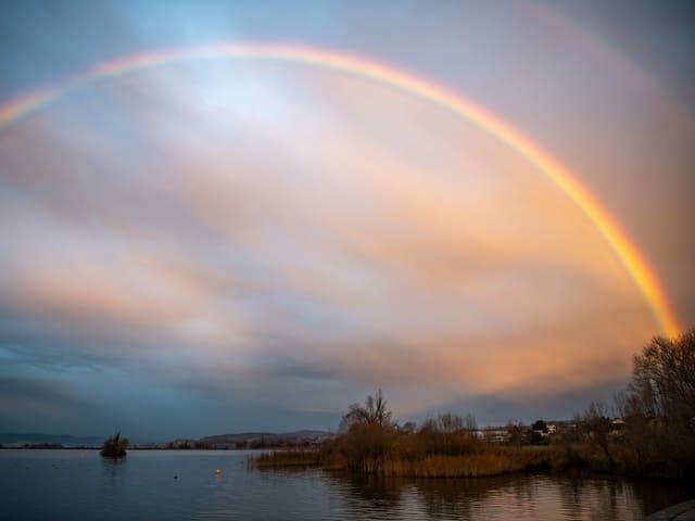 Vollständiger Regenbogen über einem See.