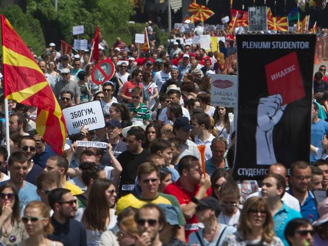 Personen mit Plakaten und Flaggen auf der Strasse.