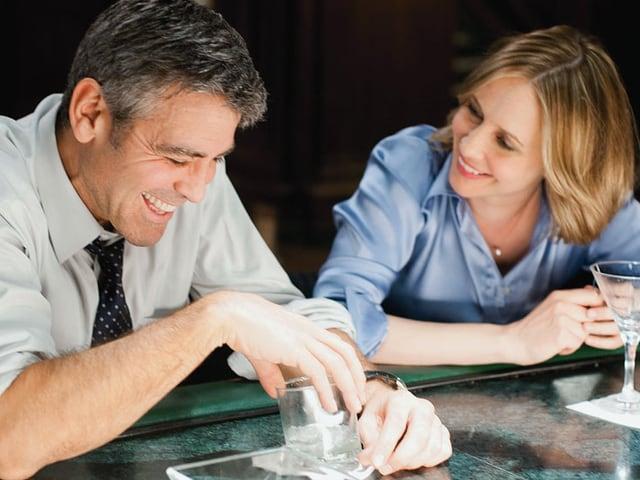 George Clooney als Ryan Bingham und Vera Farmiga als Alex Goran im Gespräch an einer Bar.