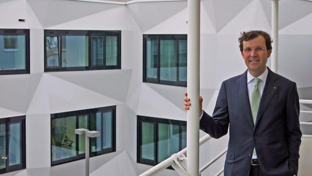 Schaltegger, ein Mann in Anzug mit Brille, steht auf einem Balkon, im Hintergrund Fenster eines weissen Gebäudes.