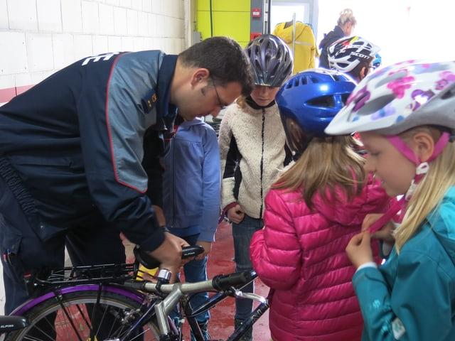 Ein Polizist und viele Kinder bei einem Fahrrad.