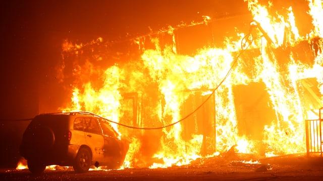 Ein Gebäude in Flammen, davor steht ein Auto.