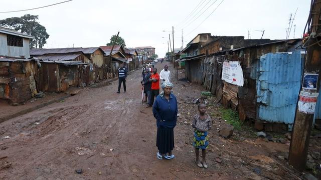 Menschen stehen auf der Strasse eines Slums in Nairobi.