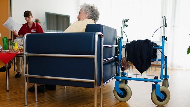 alte Frau sitzt in einem Sessel, Rollator steht daneben