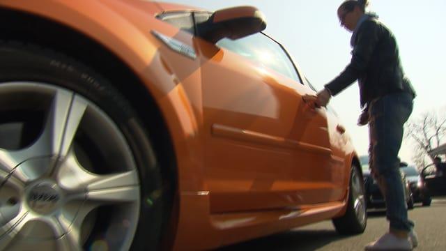 Eine junge Frau öffnet eine Autotür.