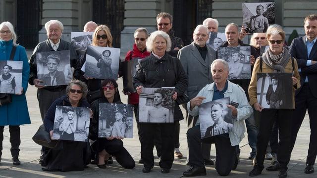 Ehemalige Verdingkinder und Opfer fürsorgerischer Massnahmen posieren mit Kinderfotos vor dem Bundeshaus.