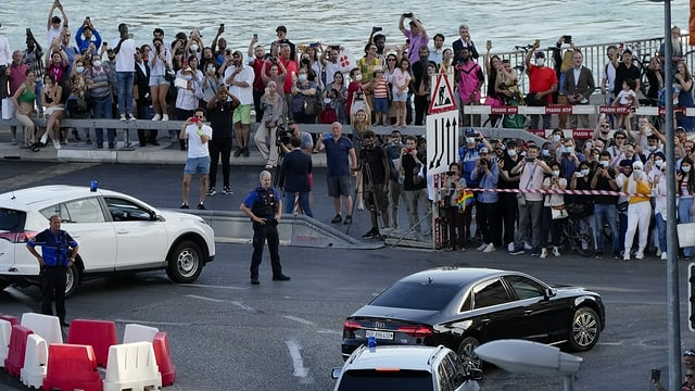 Menschenmenge beobachtet hinter Absperrung die Polizei und vorbeifahrende Autos.