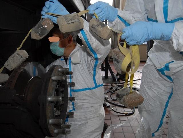 Zollfahnder ziehen an einem Band befestigte Drogensäckchen aus dem Versteck.