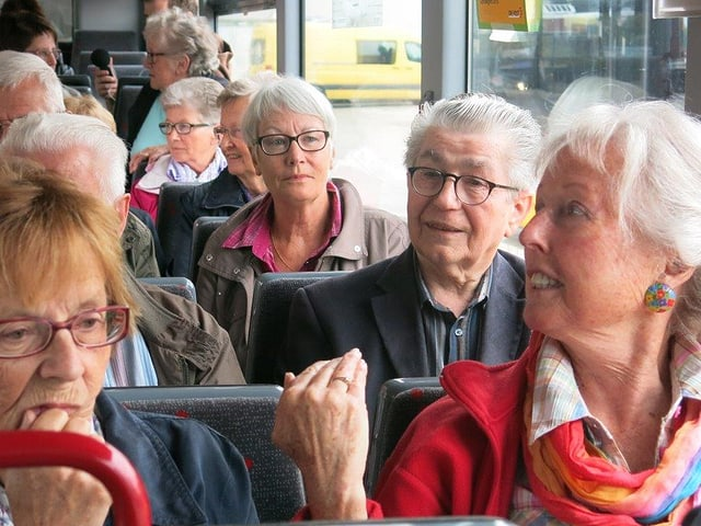 Mehrere Menschen sitzen gespannt in einem Bus.