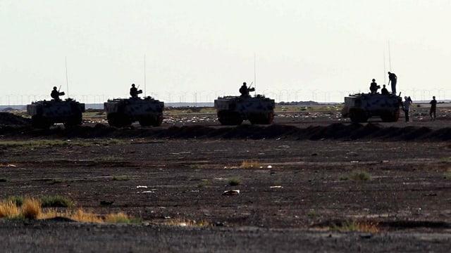 Vier Panzer mit Soldaten in der Wüste.