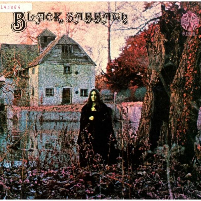 ein Foto eines Plattencovers, wo eine Frau mit langen schwarzen Haare in einem dunklen Wald steht