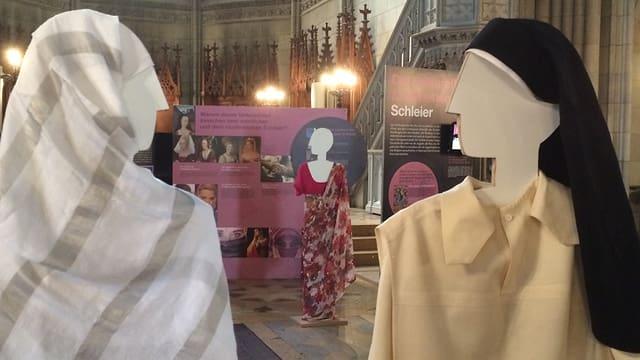 Zwei verschleierte Holzpuppen. Eingekleidet als Muslima und als Nonne.