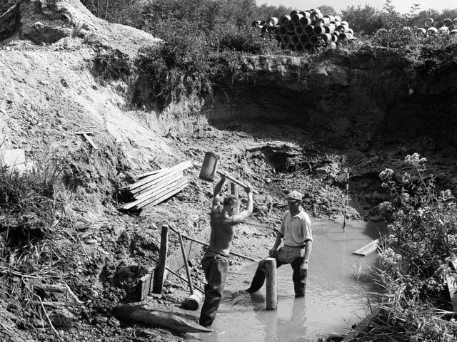 Schwarzweissbild von zwei Männern, die in einem Bach stehen und Pfähle einschlagen