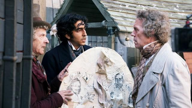 Filmszene: Drei Männer in altmodischer Kleidung stehen zusammen und halten einen Drachen in der Hand, der mit Papierfetzen beklebt ist.