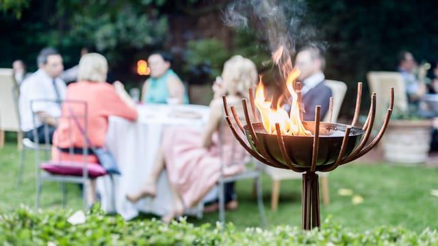 Mehrere Tische in einem Garten mit Leuten, die etwas trinken.