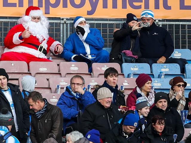 Zwei Weihnachtsmänner mischen sich unters Publikum.