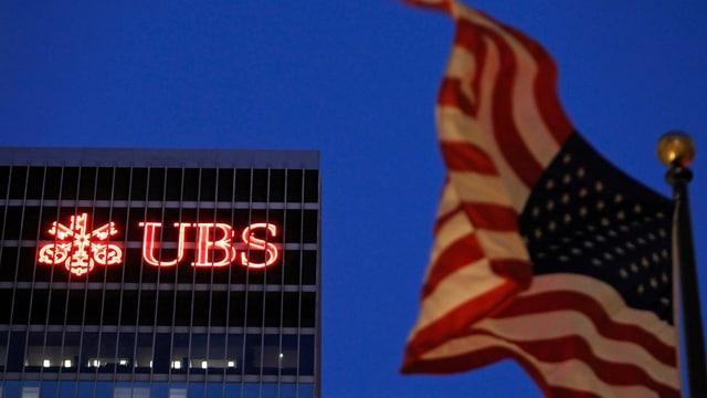 US-Fahne vor einem UBS-Gebäude in New York im Halbdunkeln.
