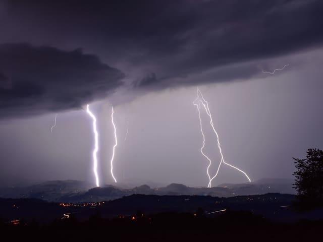 Auf diesem Foto sind gleich fünf Blitze zu erkennen, die sich zwischen Wolken und Boden entladen.