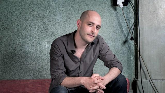 Andreas Schaerer sitzt auf einem Sofa.