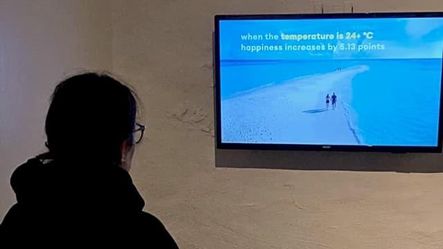 Eine Frau starrt auf einen TV an der Wand.