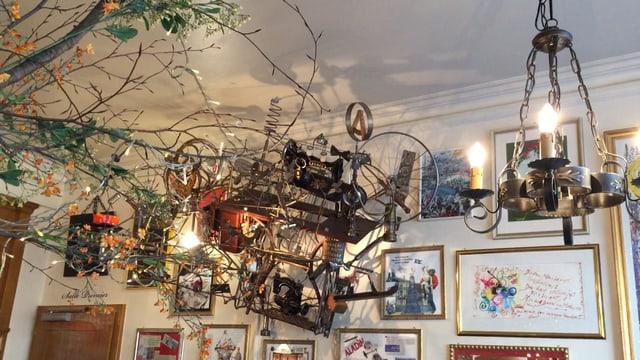 An der Decke hängt ein metallenes Kunstobjekt vor einer mit vielen gerahmten Bildern geschmückten Wand.