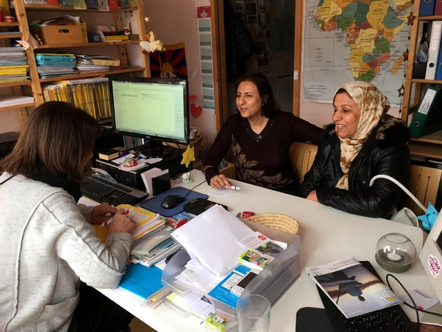 Drei Frauen sprechen an einem Tisch miteinander.