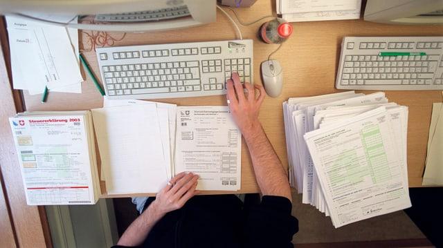 Ein Mann füllt die Stuererklärung am Computer aus.