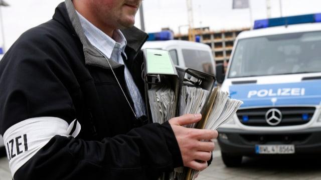 La polizia tudestga suenter ina perquisiziun d'ina chasa. In polizist porta ina pluna documents tar l'auto da polizia.