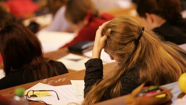 Studentin mit langem Haar sitzt mit aufgestütztem Kopf im Hörsaal