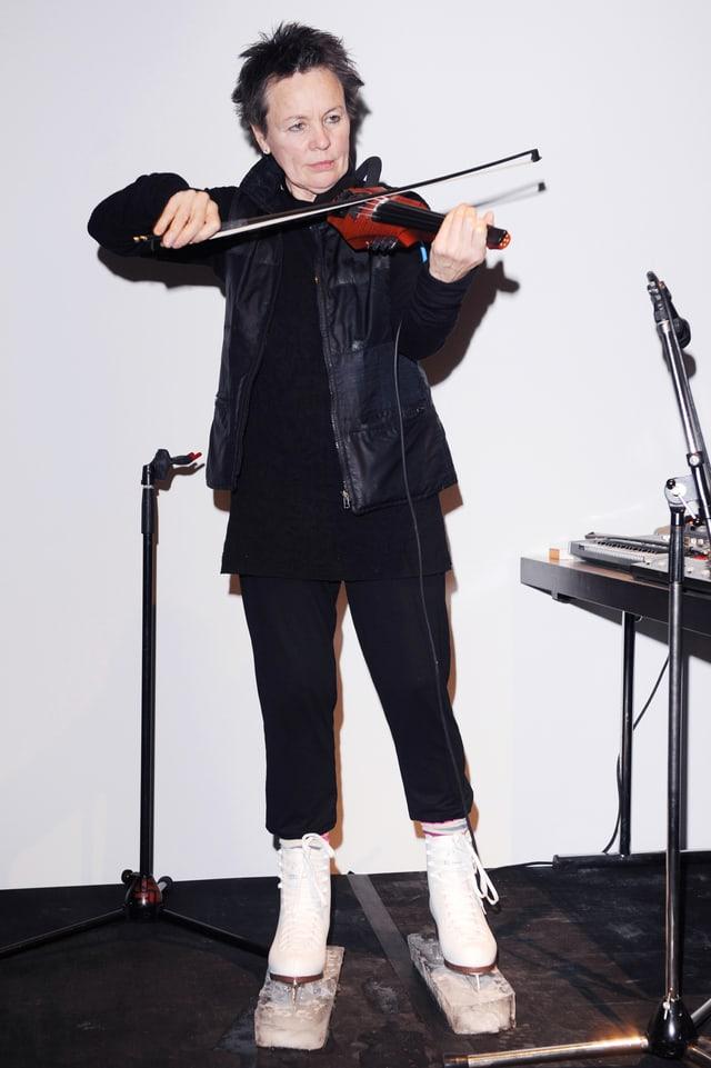 Laurie Anderson spielt Geige und trägt dabei Schlittschuhe mit Eisblöcken an den Kufen.