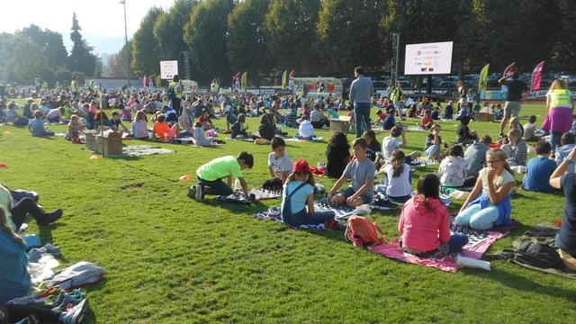 Die Schüler und Schülerinnen sitzen auf dem Sportplatz