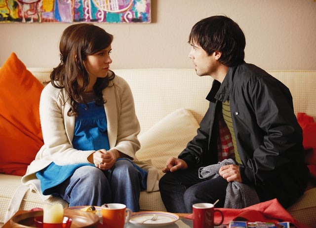 Eine junge Frau und ein junger Mann sitzen auf einem Sofa und schauen sich gegenseitig an.