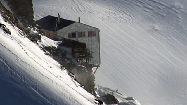 Eine SAC-Hütte oberhalb eines Schneefeldes.