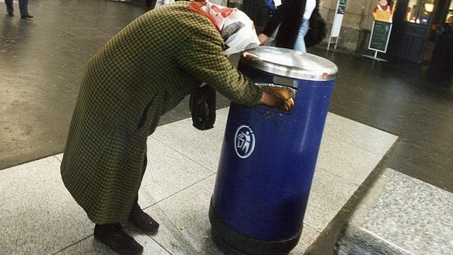 Eine Frau durchsucht einen Abfalleimer im Bahnhof Zürich.