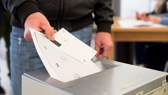Ein Mann wirft Abstimmungszettel in eine Urne.