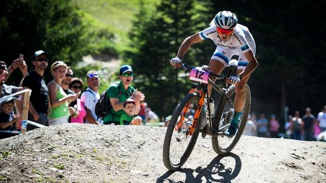 Jolanda Neff sin in mountainbike sin ina via alpestra. Davostiers public che applaudescha.