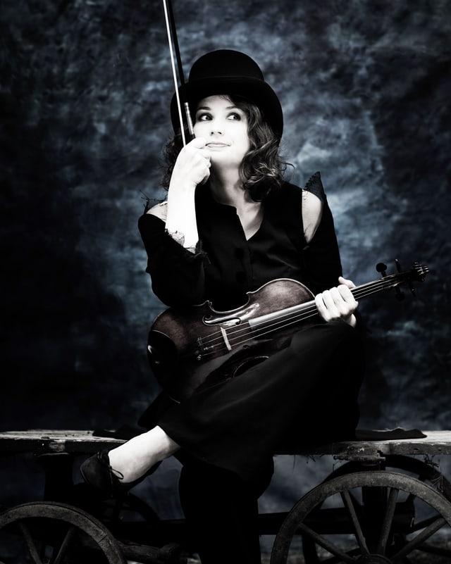 Frau mit Geige und Bogen sitzt auf einem Leiterwagen.