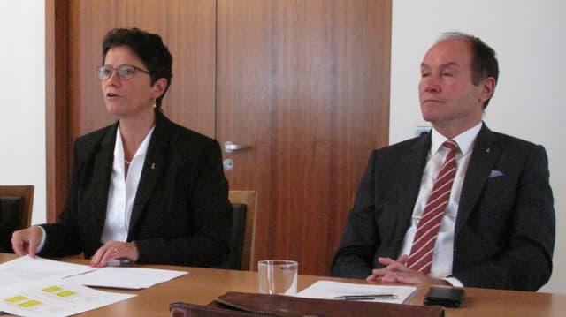 Zwei Männer und eine Frau an einem Tisch. Sie referiert.