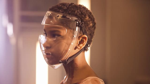 Ein Mädchen mit einer umgebundenen Plastikmase